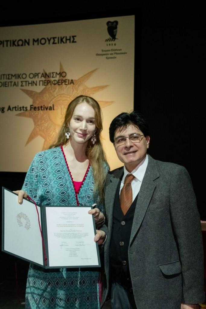 Ο επίτιμος πρόεδρος της ΕΕΘΜΚ Κυριάκος Λουκάκος απονέμει το Βραβείο σε Πολιτισμικό Οργανισμό Μουσικής της Περιφέρειας 2018 στην κα Paula Schwartz του Samos Young Artists Festivalpg